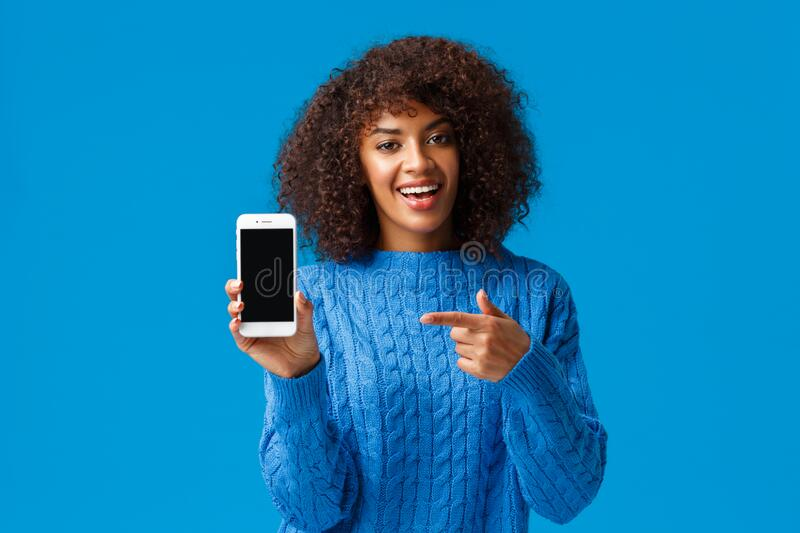 Check this out. Happy charismatic african-american woman with afro haircut, holding smartphone, showing mobile screen royalty free stock photo