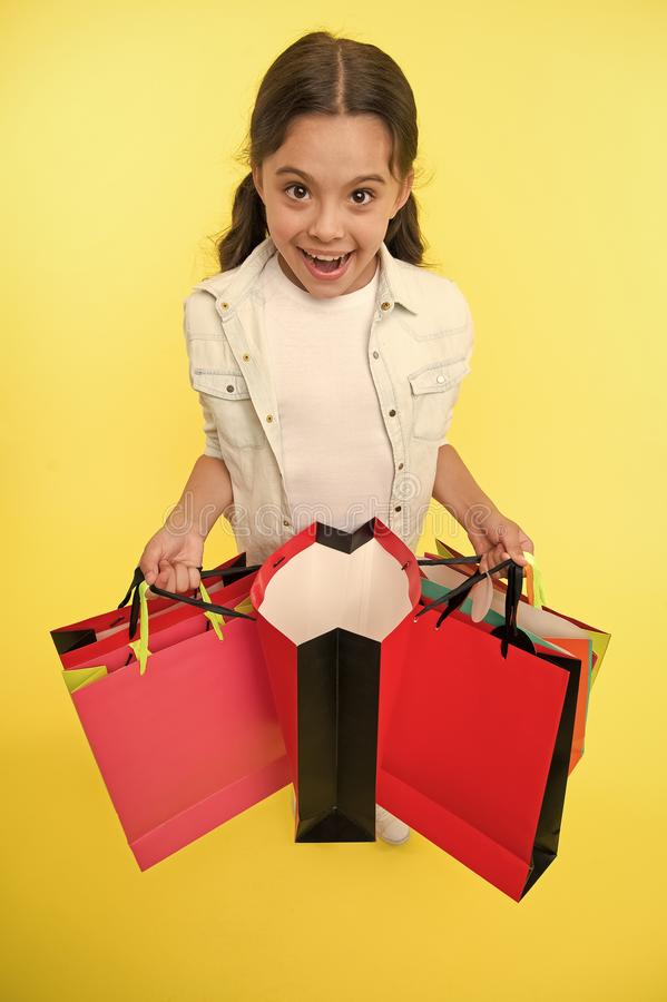 Check out her profitable purchases. Girl carries shopping bags yellow background. Girl fond of shopping. Child cute. Shopaholic with bunch shopping bags black stock images