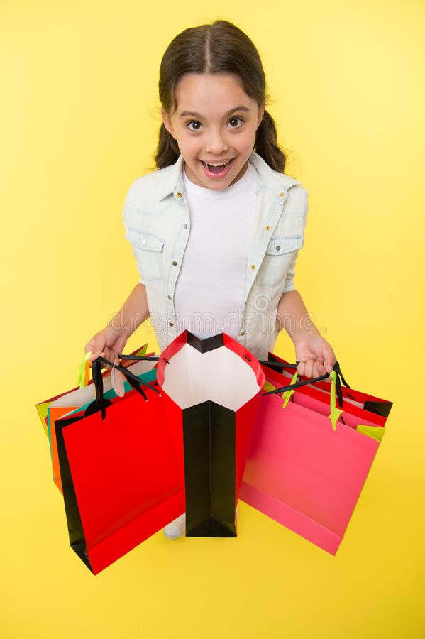 Check out her profitable purchases. Girl carries shopping bags yellow background. Girl fond of shopping. Child cute. Shopaholic with bunch shopping bags black royalty free stock images