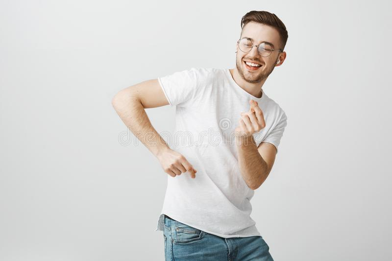 Check out my moves. Carefree delighted and happy young male student with beard in glasses and white t-shirt dancing stock image