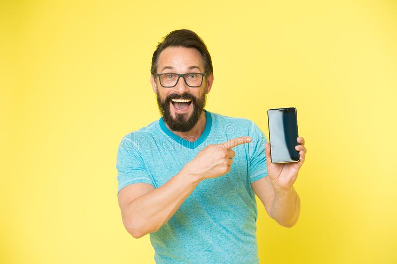 Check out new app. Guy eyeglasses cheerful pointing at smartphone. Man happy user recommends try application for royalty free stock image