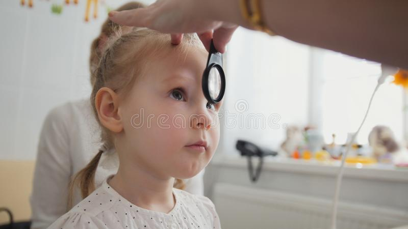 Check up of eyesight in child`s ophthalmology - optometrist diagnosis little girl. Close up royalty free stock images