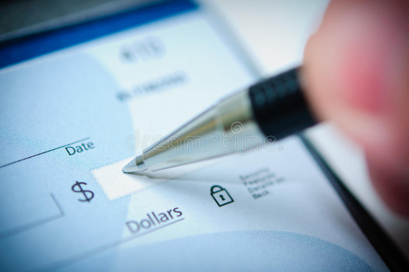 Check Writing. Writing a check with a pen stock photo