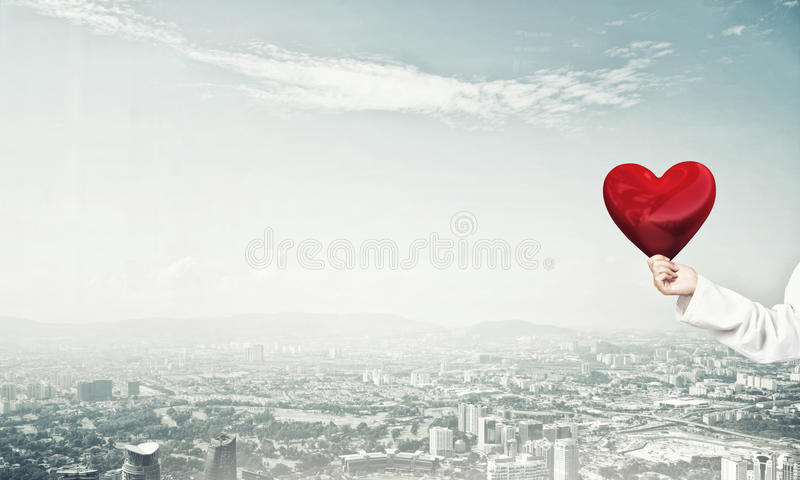 Check your heart. Close view of woman doctor against city background holding red heart stock photos