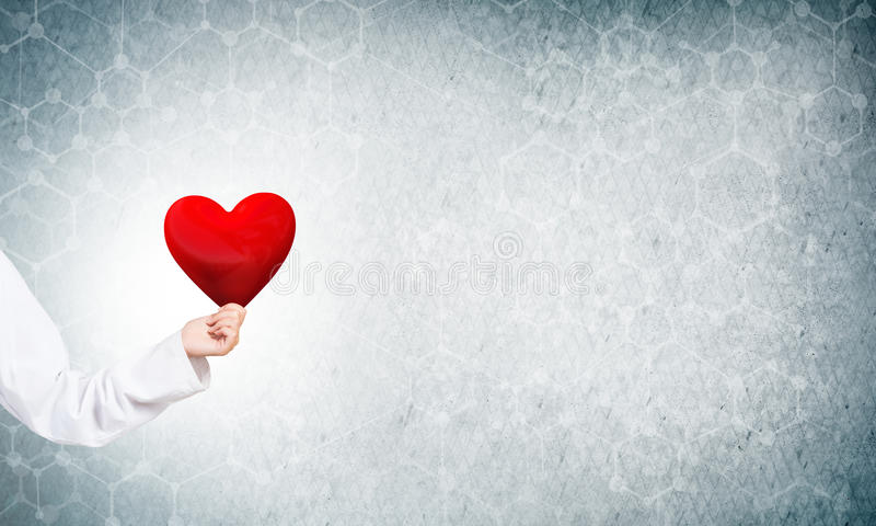 Check your heart. Hand of woman doctor against blue background holding red heart stock image