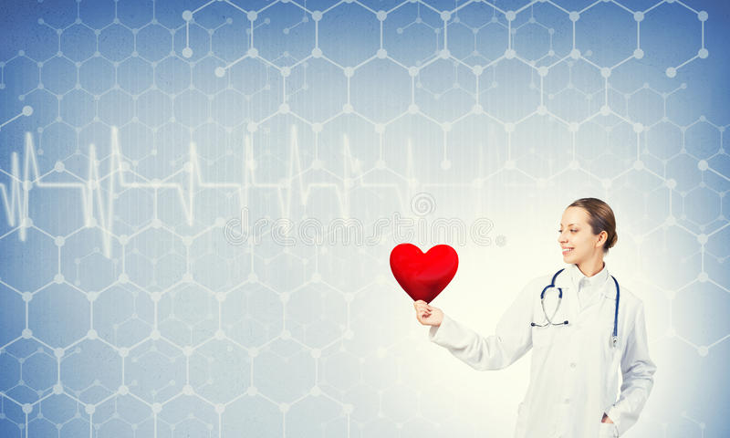 Check your heart. Young woman doctor against blue background holding red heart royalty free stock image