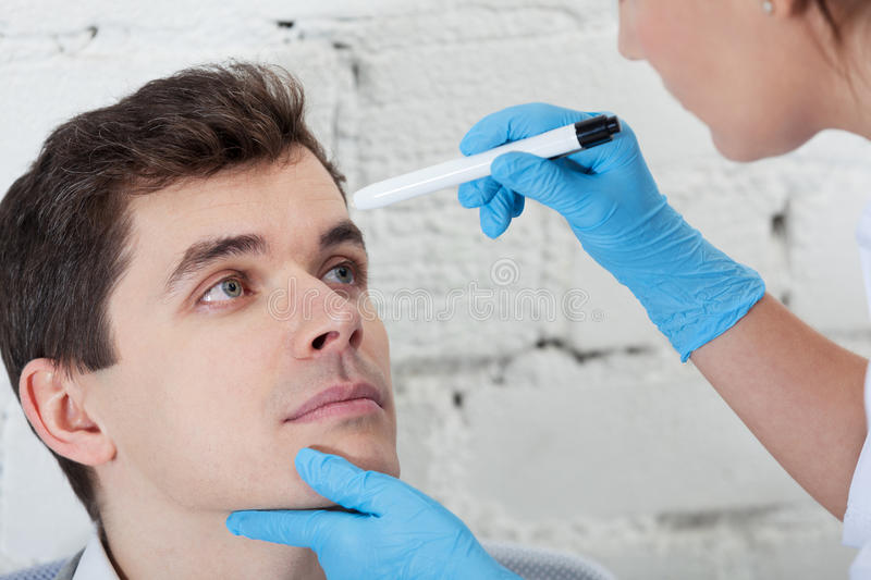 Check your tired eyes. Doctor checking tired eyes of patient royalty free stock photos