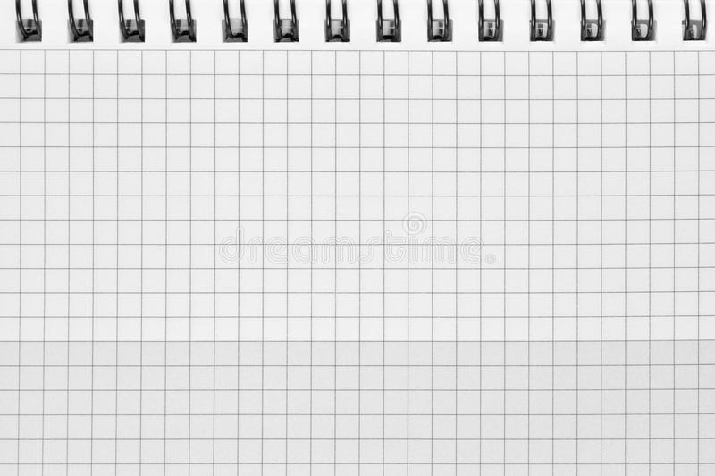 Checked spiral notebook background pattern, horizontal chequered squared open notepad copy space, stapled blank empty blocknote royalty free stock photos
