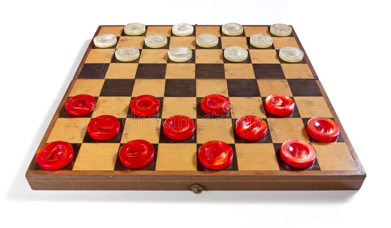 Checkerboard with Red and White Pieces. Old checkerboard on a white background with red and white pearly pieces in the starting position royalty free stock photo