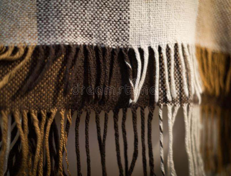 Checkered brown and white plaid with fringe. Woolen checkered plaid. Plaid photographed with shallow depth of field royalty free stock photos