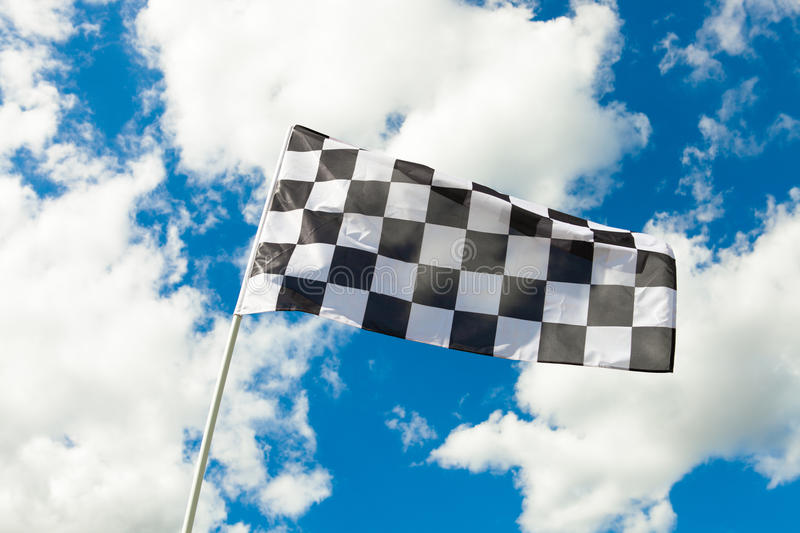Checkered flag waving in the wind with clouds on background - outdoors shoot royalty free stock photography