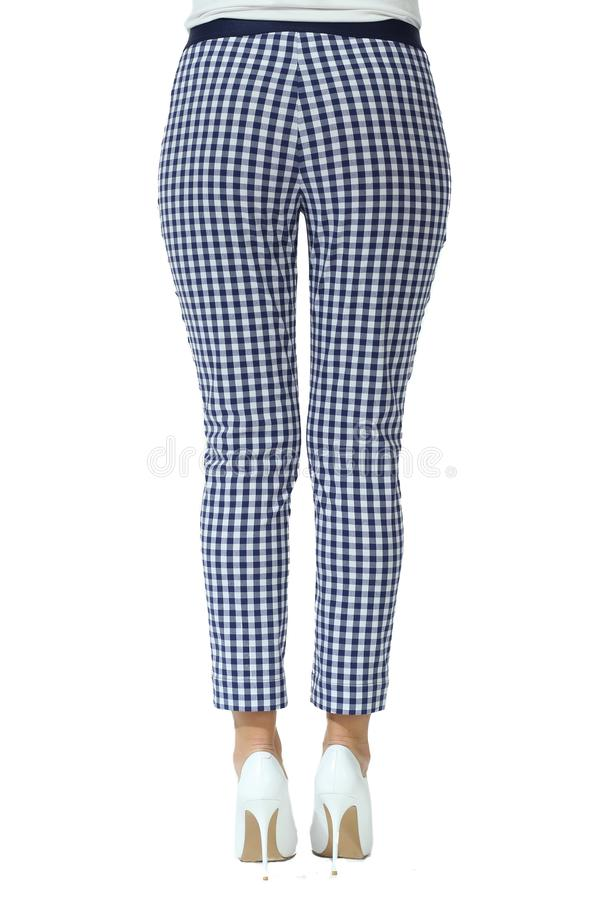 Checkered formal trousers on model legs with white stiletto heels. Shoes isolated on white stock images