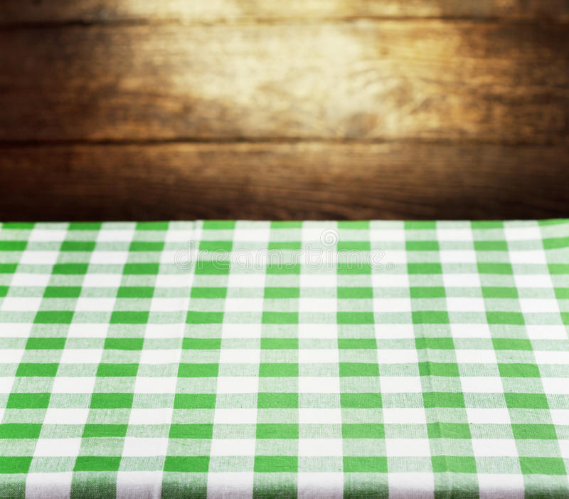 Checkered green tablecloth over wooden background. Checkered green tablecloth over rustic wooden background stock images