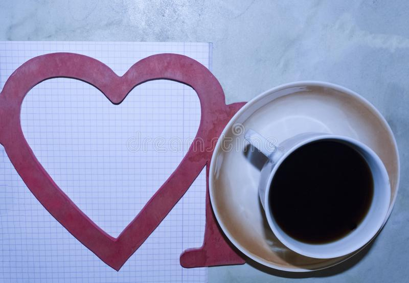 The word love, a Cup of coffee, a heart, a leaf with a pen. royalty free stock photography