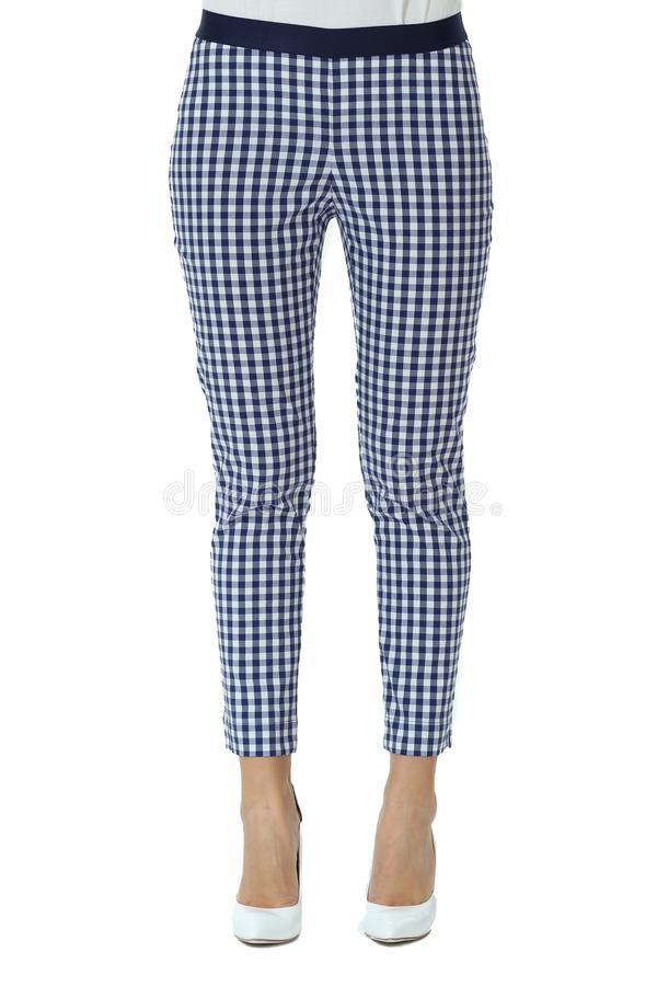 Checkered official trousers with belt on model legs with white stiletto heels. With bare toes royalty free stock photo