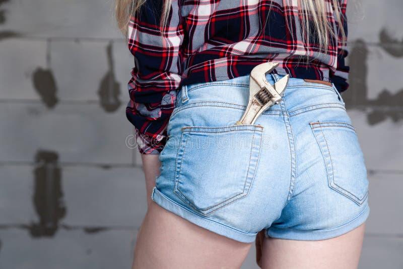 Задняя часть девушки крупного плана, ключ в кармане голубых прозодежд джинсов джинсовой ткани, checkered рубашке Oncept ¡ Ð ремон стоковые изображения