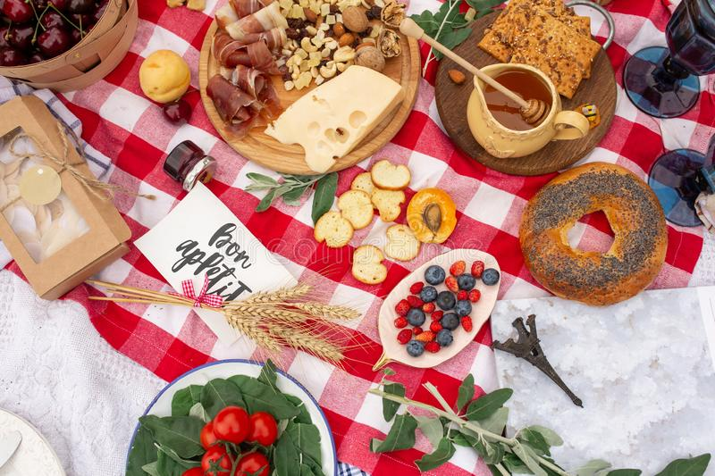 Checkered picnic blanket in french style with foods and sign says bon appetit.  royalty free stock images