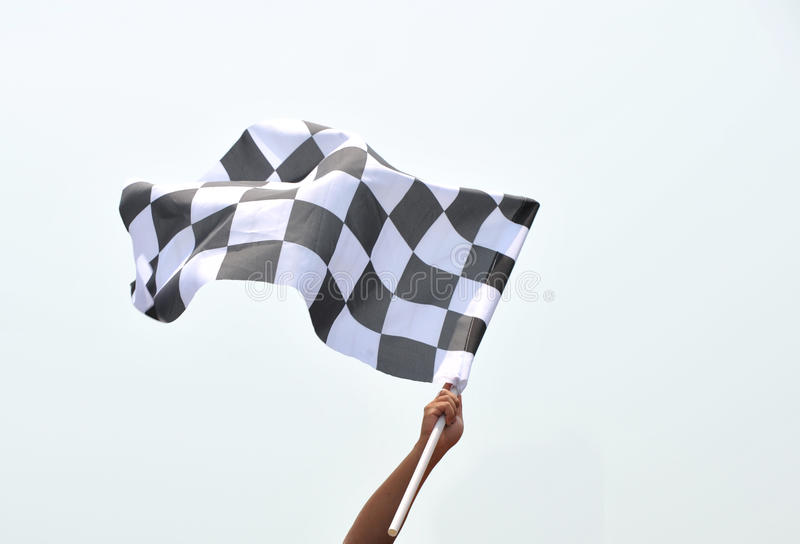 Checkered racing flag. Checkered race flag in hand royalty free stock image