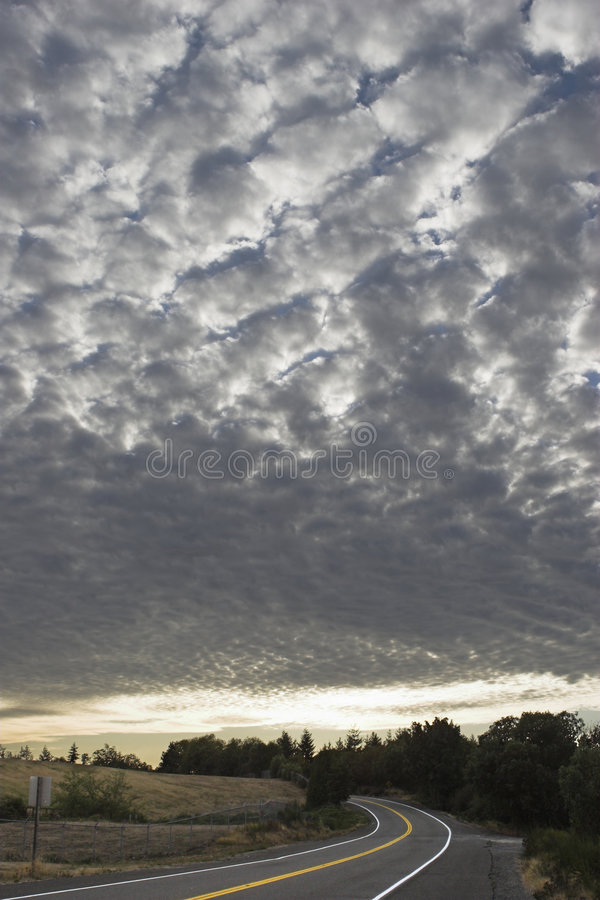 Checkered sky above road stock photography