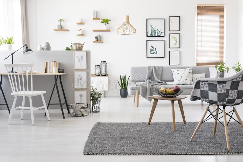 Checkered, stylish chair on a gray rug in a spacious, scandinavian living room interior with mock-up gallery above a sofa royalty free stock image