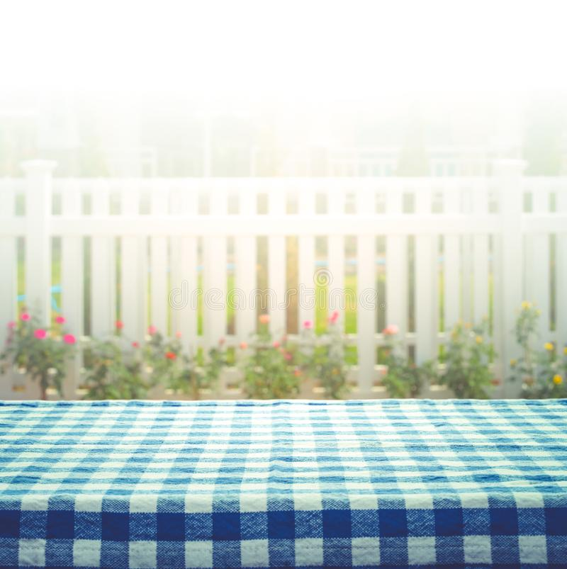Checkered tablecloth on blur of white fence and garden background royalty free stock photo