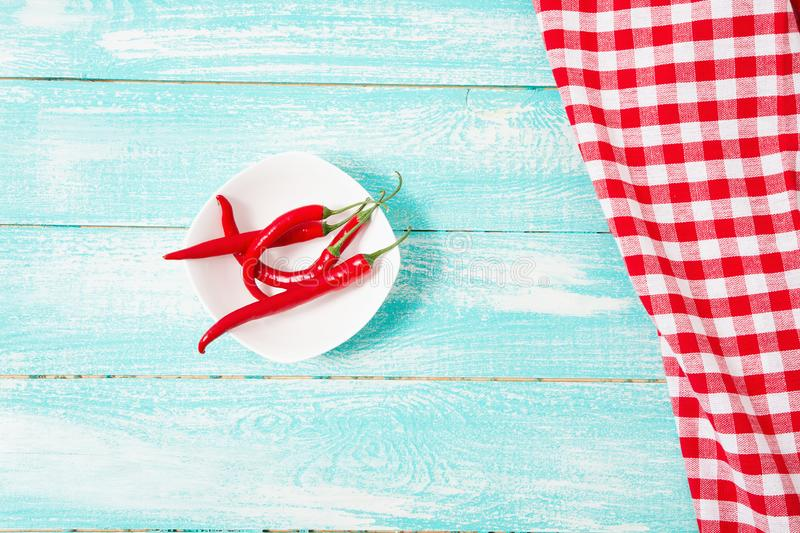Checkered tablecloth,red hot pepper on blue wooden desk. Copy space stock image