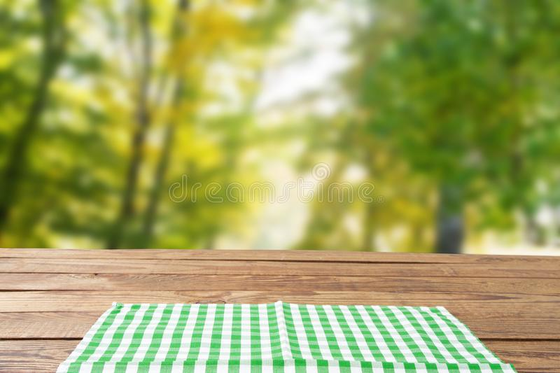 Checkered tablecloth top view with blur abstract green bokeh design garden. Selective focus. Copy space. Place for food and drink stock photo