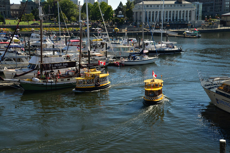 Checkered Water Taxis on Victoria's landmark waterfront, Victoria. Taxis ply back and forth on the channel in the busy Victoria waterfront stock photography