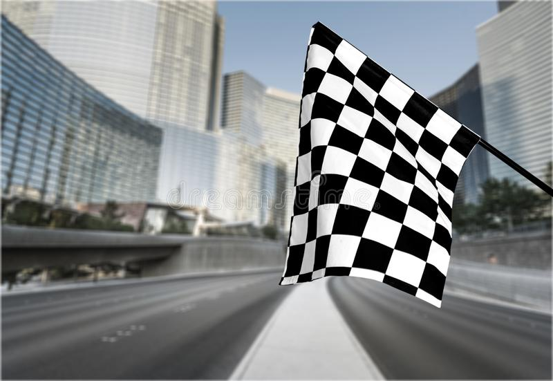 Checkered waving flag on city background. Concept. Flag waving check checkered checker chequered flag car racing stock photo