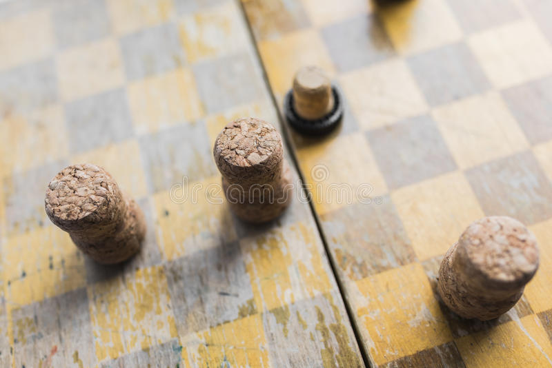 Checkers game with wine stoppers. Old wooden wine corks on a chessboard are used instead of chess. Victory over alcoholism. Bar games concept stock photos