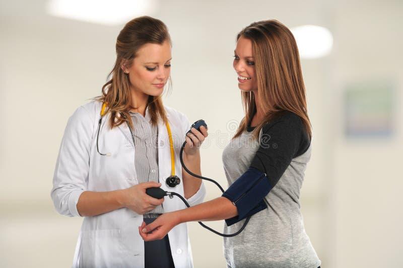年轻Checking医生患者 免版税库存图片
