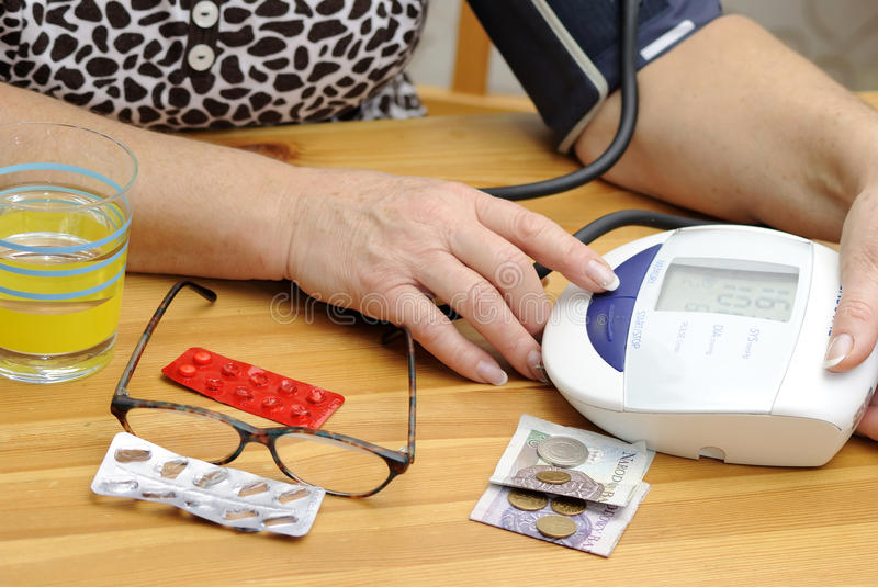 Checking blood pressure. Pensioner women is checking for blood pressure stock images