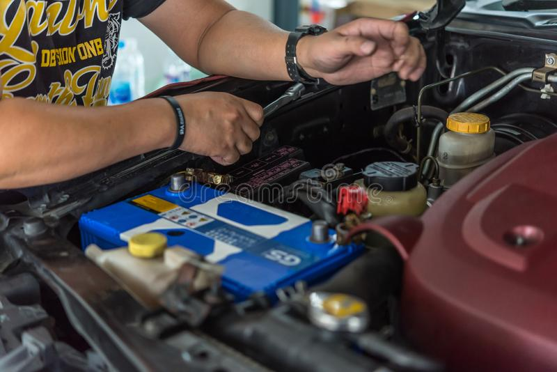 Checking a car battery for repair at car garage. Bangkok, Thailand - August 5, 2017 : Unidentified car mechanic or serviceman checking a car battery for fix and stock images