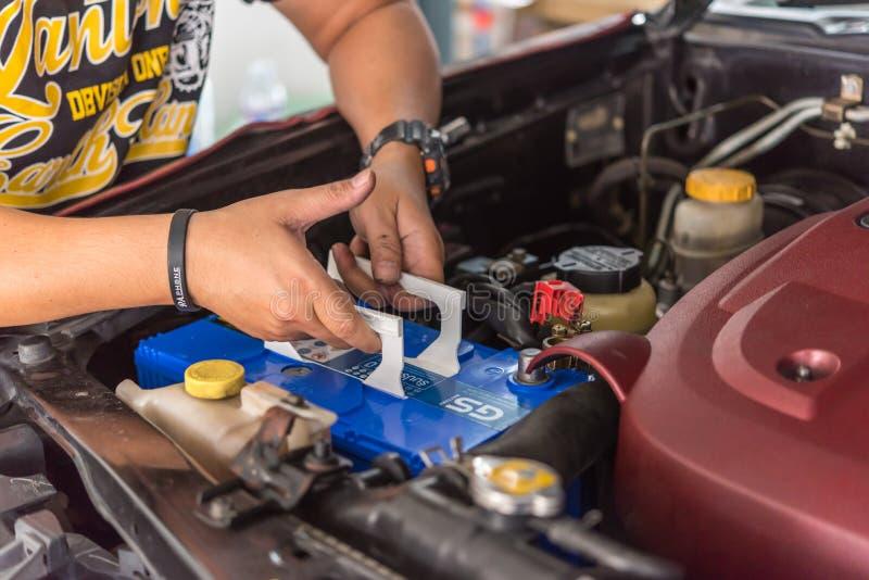 Checking a car battery for repair at car garage. Bangkok, Thailand - August 5, 2017 : Unidentified car mechanic or serviceman checking a car battery for fix and stock photo