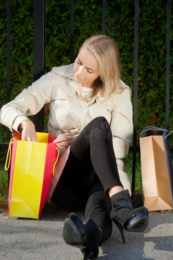 Checking catch. Attractive woman checking catch from shopping mall stock photo