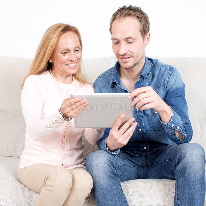 Checking an electronic devise. Younger men with elderly women checking an electronic devise stock photography