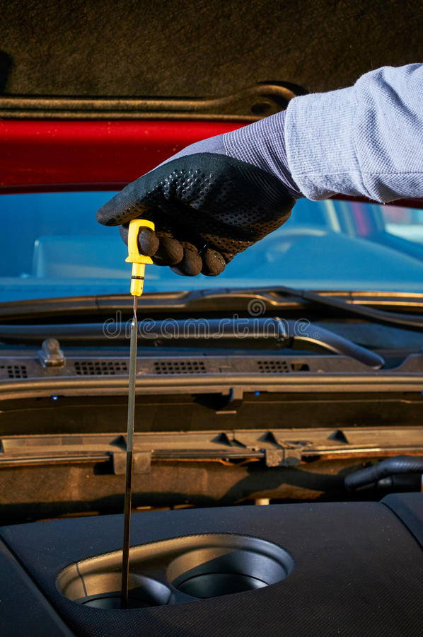 Checking engine oil level in modern car. Winter service for safe driving. stock photography