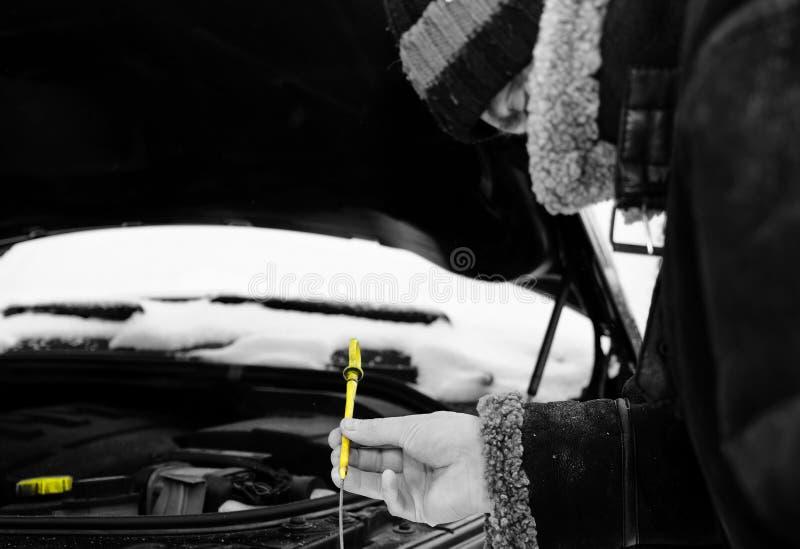 Checking Engine Oil. Selective color shot of a man checking engine oil with dipstick, winter shot stock photos