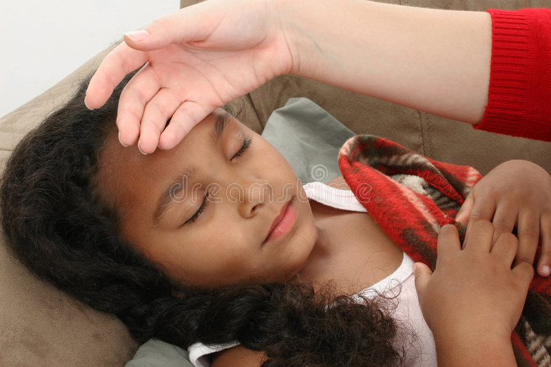 Checking for fever. Mother's hand feeling little girl's forehead. Checking for a fever royalty free stock photo