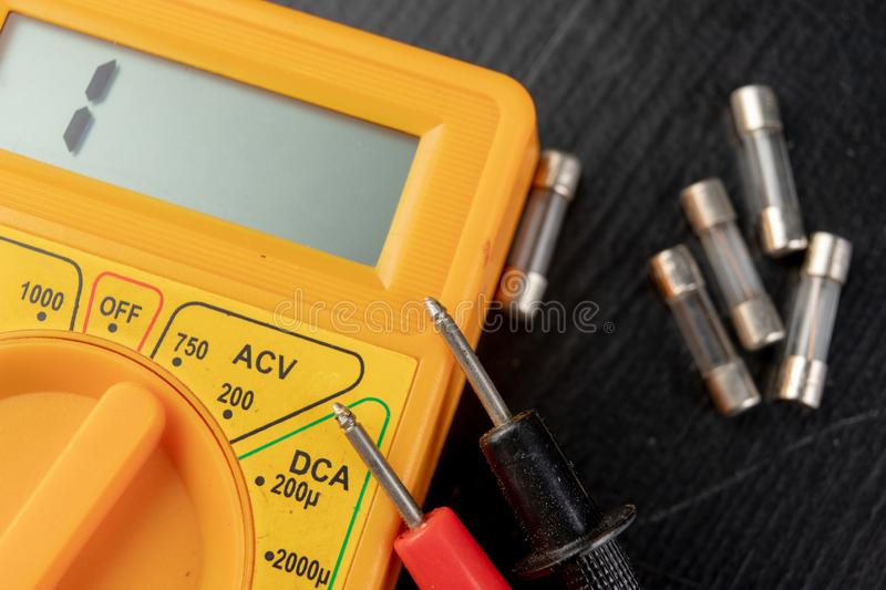 Checking glass fuses using the meter. Simple electrical work in a home workshop stock images