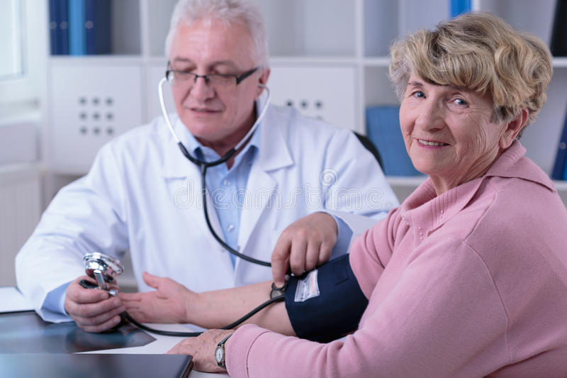 Checking the hypertension. Aged doctor checking older woman's hypertension stock photos