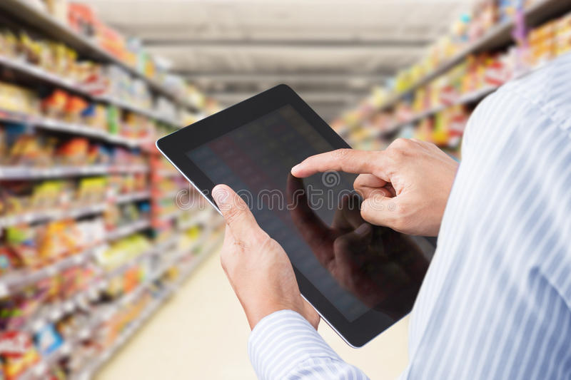 Checking inventory in minimart on touchscreen tablet royalty free stock photos