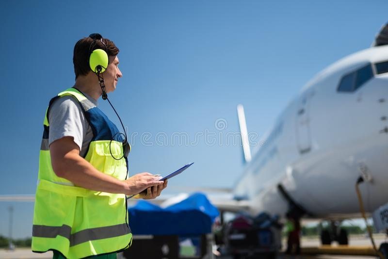 Airport worker looking at passenger plane. Checking the jet. Side view of airport crew member. Man wearing headphones and holding the clipboard stock photos