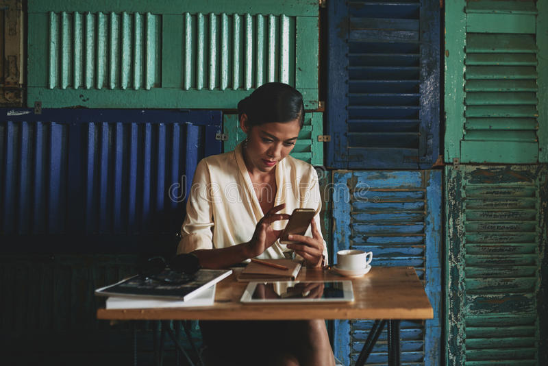 Checking mail. Business woman sitting in atmospheric cafe and checking mail on her smartphone stock photography