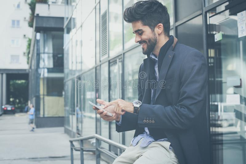 Checking the mail over the phone. Business man using smart phone n city street stock photography