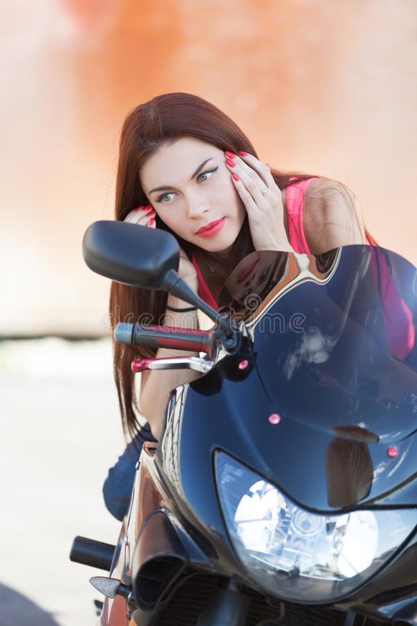 Checking make up. Girl on sport bike checking make up royalty free stock photo