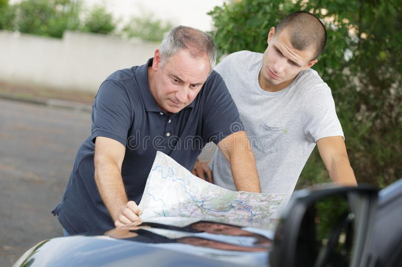 Checking map on car. Checking the map on the car royalty free stock photos