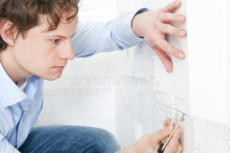 Checking measurements. Engineer meticulously checking measurements on a technical drawing using a pair of compasses royalty free stock photography