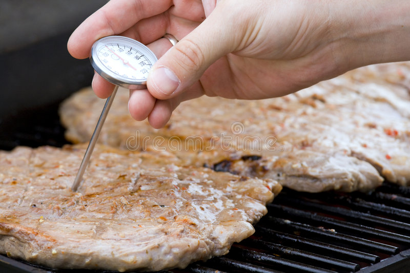 Checking meat. Temperature while grilling stock photo
