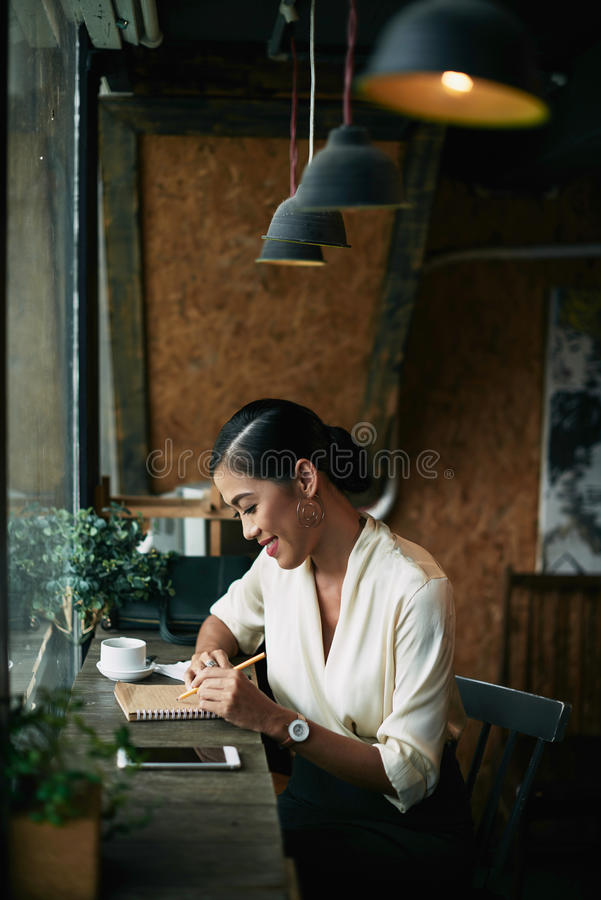 Checking notes. Smiling business woman checking her notes when sitting in cafe stock photos